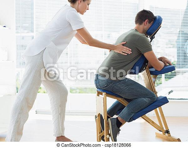 Female therapist massaging man in hospital - csp18128066