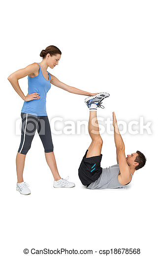 Female trainer assisting man with exercises - csp18678568