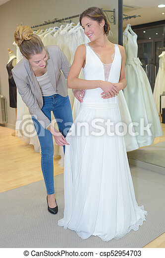 Female Trying Wedding Dress In A Shop With Women Assistant