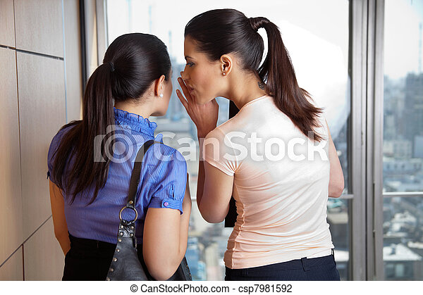 Female Whispering to Co-worker - csp7981592