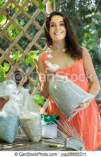 Female with fertilizer at garden - csp28800311