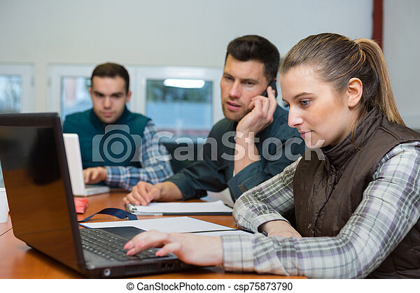 female worker showing data in laptop to warehouse worker - csp75873790