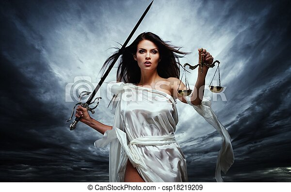 Femida, Goddess of Justice, with scales and sword against dramatic stormy sky - csp18219209