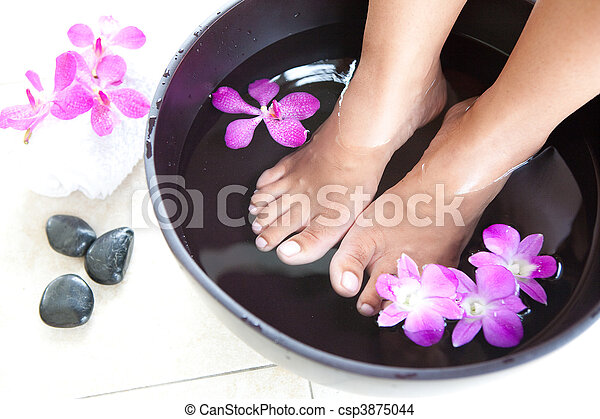 Feminine feet in foot spa bowl with orchids - csp3875044