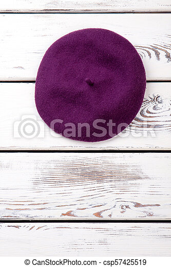 7755e35d3f6 Feminine wool beret and copy space. purple french beret for women on white  wooden background. fashion accessory and femininity.