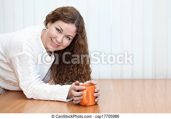 femme, copyspace, bureau, jeune regarder, grande tasse, appareil photo, mains, orange, table - csp17705986