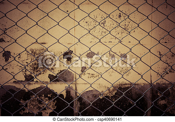 Fence from steel mesh on grunge cement wall backgroud with vintage filter - csp40690141