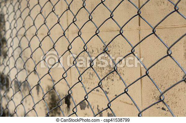 Fence from steel mesh on grunge cement wall backgroud - csp41538799