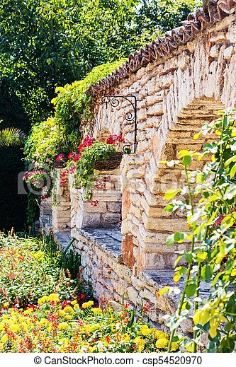 fence white bricks, green grass and red flowers - csp54520970