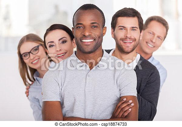 ficar, olhar, mantendo, team., grupo, pessoas negócio, braços, jovem, alegre, confiante, atrás de, câmera, enquanto, africano, cruzado, homem sorridente, ele, fila - csp18874733