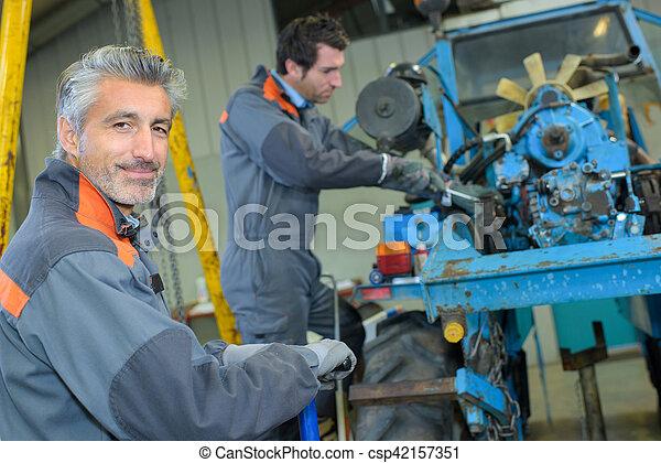 Arreglando un tractor - csp42157351