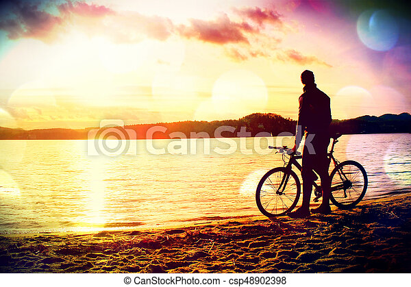 Film grain  Young man cyclist silhouette on blue sky and sunset background  on the beach  End of season at lake