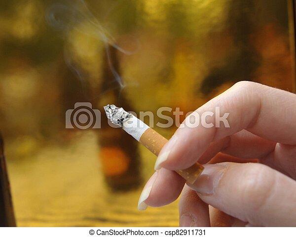 Filter cigarette smoker holding cigarette in hand - csp82911731