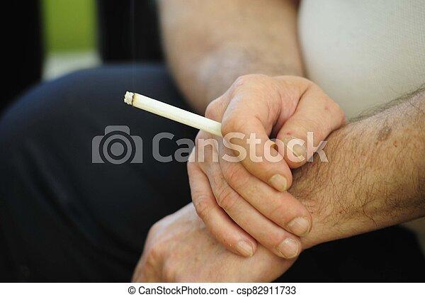Filter cigarette smoker holding cigarette in hand - csp82911733