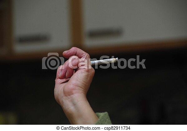 Filter cigarette smoker holding cigarette in hand - csp82911734