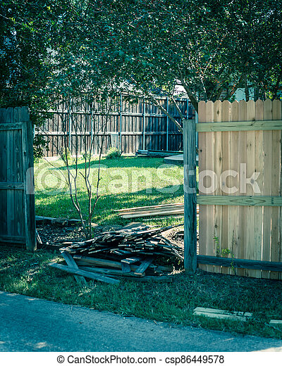 Filtered image aged wooden fence near new lumber boards installation of suburban residential house in Texas, USA - csp86449578