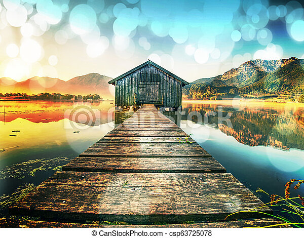Filtered. Old wooden ship house at scenic Lake. Silent bay - csp63725078