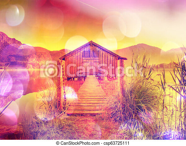 Filtered. Old wooden ship house at scenic Lake. Silent bay - csp63725111