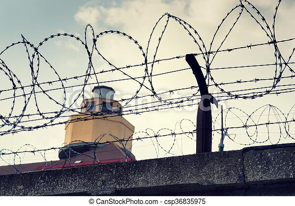 Filtered vintage guarding tower behind barbed wire fence prison walls.