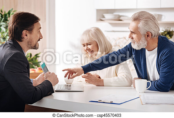 Finance advisor meeting with elderly couple of clients - csp45570403