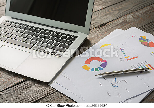 Financial charts on the table with laptop - csp26929634