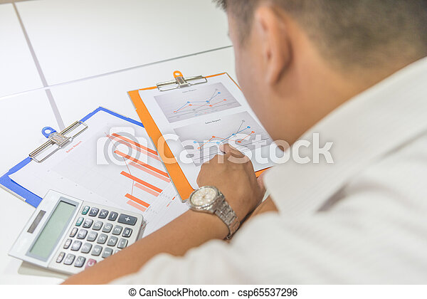 Un joven hombre de negocios comprobando los registros financieros en la oficina - csp65537296