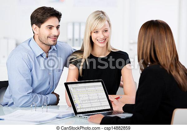 Pareja sonriendo mientras busca asesor financiero en el escritorio - csp14882859