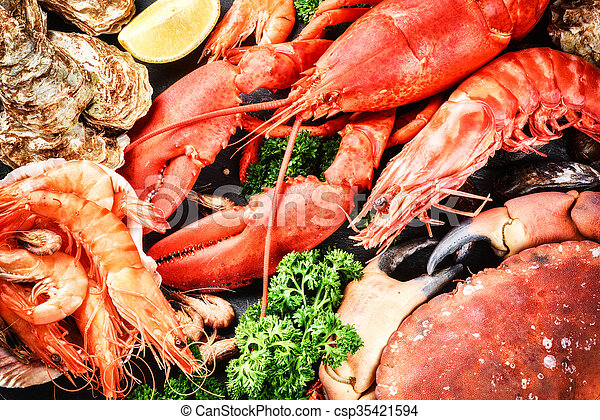Fine selection of crustacean for dinner. Lobster, crab and jumbo shrimps and oysters - csp35421594