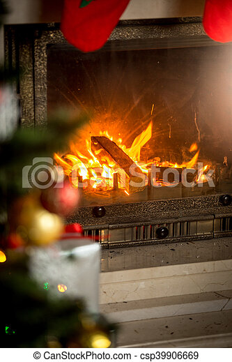 Fireplace with with burning wood logs decorated for Christmas - csp39906669