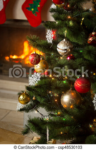 Fireplace with with burning wood logs decorated for Christmas - csp48530103