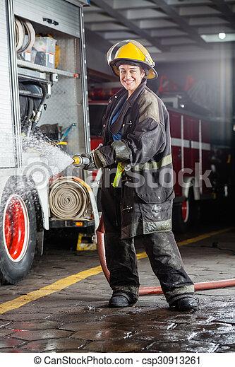 Feliz bombero rociando agua durante la práctica - csp30913261