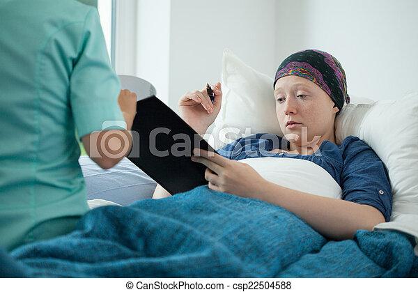 Mujer cáncer firmando documentos - csp22504588