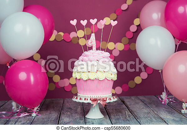 First Birthday Cake With A Unit On Pink Background Balls And Paper Garland