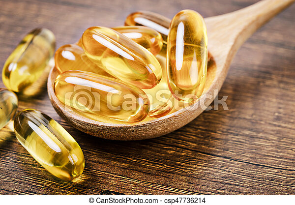 Fish oil capsules with omega 3 and vitamin D in a wooden spoon. - csp47736214