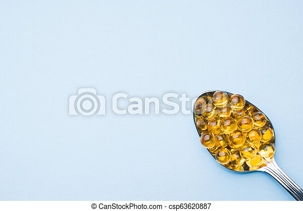 Fish oil capsules with omega 3 and vitamin D blue texture, healthy diet concept, selective focus. - csp63620887
