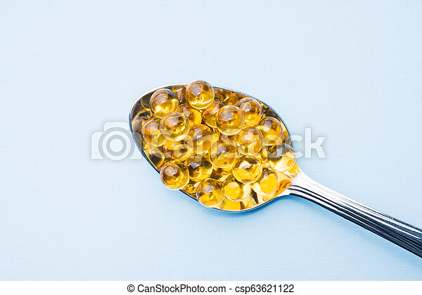 Fish oil capsules with omega 3 and vitamin D blue texture, healthy diet concept, selective focus. - csp63621122