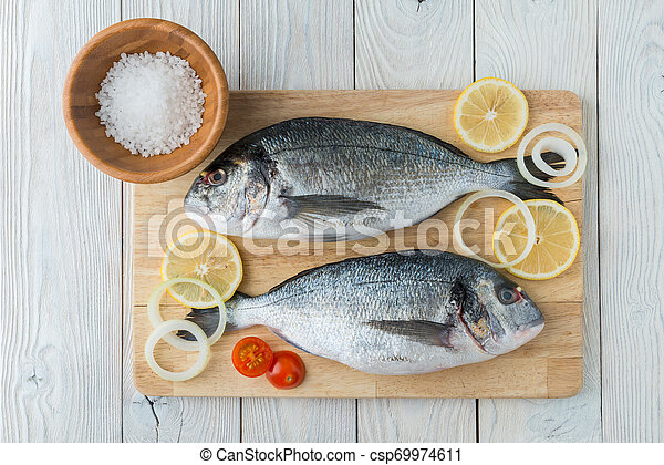 fish with spices on a wooden background - csp69974611