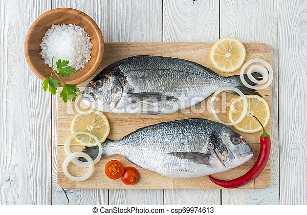 fish with spices on a wooden background - csp69974613