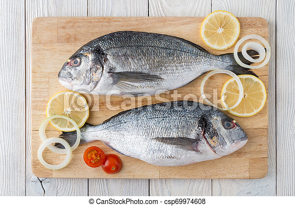 fish with spices on a wooden background - csp69974608