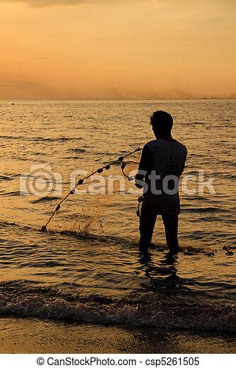 Fisherman at beach with fishing net - csp5261505
