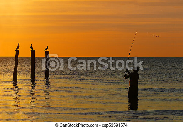 Fisherman casting his line in the Gulf of Mexico at sunset - Fort Myers Beach, Florida - csp53591574