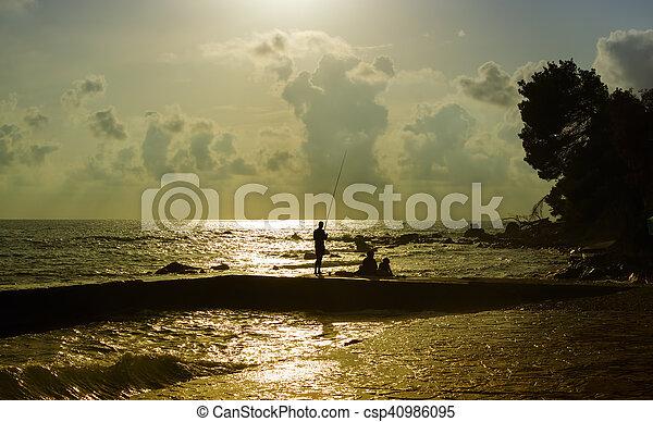 Fisherman silhouette in last rays of sunlight. - csp40986095