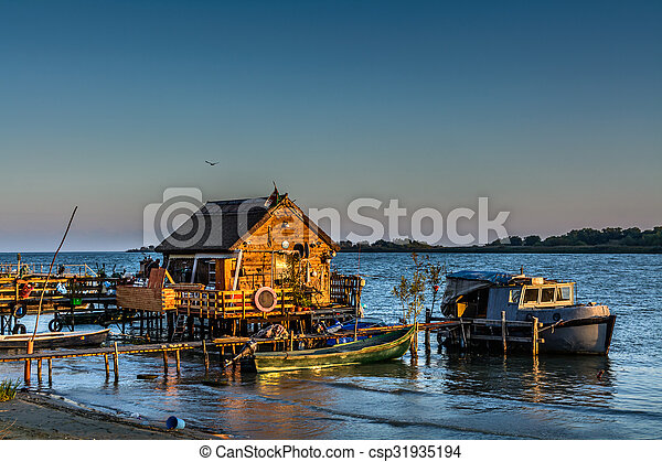 Fisherman's House, the old dock and the boat on the lake. Rustic landscape with wooden pier in the summer evening. - csp31935194