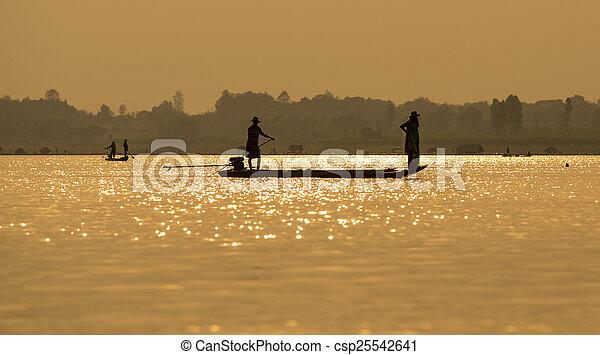 Fishermen in the boat sunrise - csp25542641