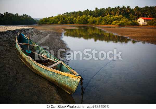 fishing boat on the river bank in the tropics with palm trees in the evening, - csp78566913