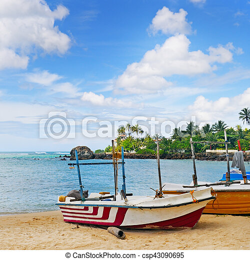 fishing boat on the sandy shore against a background the ocean and blue sky - csp43090695