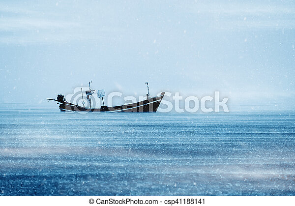 Fishing boat on the sea with snowfall in winter color tone. - csp41188141
