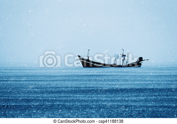 Fishing boat on the sea with snowfall in winter color tone. - csp41188138