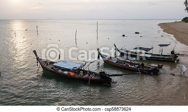 Fishing boat parked on the sea shore - csp58873624