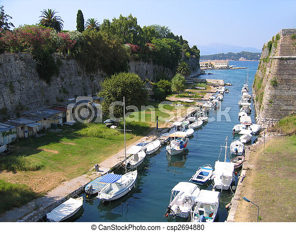 Fishing boats in canal outside old fortress - csp2694880